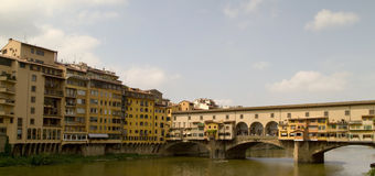 Ponte Vecchio Florence Italy. Arno river in Florence Italy with houses and The Ponte Vecchio Bridge. All signs and IDs cloned out Royalty Free Stock Photos