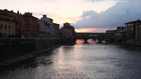 Ponte Vecchio in Florence Italy at sunset. Evening view of Ponte Vecchio old bridge over the Arno river from Ponte alle Grazie at colorful sunset. Famous stock video footage