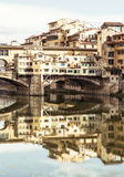Ponte Vecchio and historic buildings are mirrored in the river A Royalty Free Stock Images