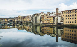 Ponte Vecchio and historical buildings are mirroring in the rive Royalty Free Stock Images