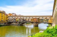 Ponte Vecchio, ponte di pietra medievale dell'arco sopra Arno River e con molti piccoli negozi lungo, Firenze, Toscana fotografia stock