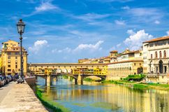 Ponte Vecchio stone bridge with colourful buildings houses over Arno River blue reflecting water and embankment promenade in histo stock photography