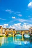 Ponte Vecchio stone bridge with colourful buildings houses over Arno River blue reflecting water in historical centre of Florence. City, blue sky white clouds royalty free stock photography