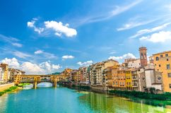 Ponte Vecchio stone bridge with colourful buildings houses over Arno River blue turquoise water and embankment in Florence. Ponte Vecchio stone bridge with stock photo