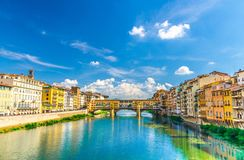 Ponte Vecchio stone bridge with colourful buildings houses over Arno River blue turquoise water in Florence. Ponte Vecchio stone bridge with colourful buildings royalty free stock photos