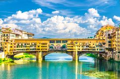 Ponte Vecchio stone bridge with colourful buildings houses over Arno River blue turquoise water in Florence. Ponte Vecchio stone bridge with colourful buildings stock photo
