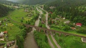 Ponte velha da opinião aérea do zangão sob o rio e a estrada Floresta da montanha da metragem do voo filme
