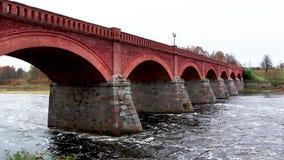 Ponte velha do tijolo através do rio Venta na cidade do vídeo do timelapse de Kuldiga Letónia video estoque
