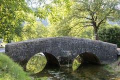 Ponte velha perto da vila medieval de les Messieurs dos Baume em França imagem de stock