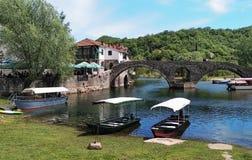 Ponte velha sobre o rio de Crnojevica, o Rijeka Crnojevica, e a área de turista perto da ponte, Montenegro foto de stock royalty free