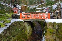 A ponte vermelha de madeira na neve do inverno Imagem de Stock Royalty Free