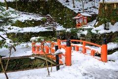 A ponte vermelha de madeira na neve do inverno Imagens de Stock Royalty Free