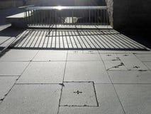 Pontevedra, Espanha; 08/09/2018: A luz solar brilha através da cerca do metal e faz sombras geométricas das listras na terra de p fotografia de stock