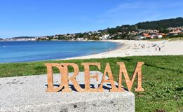 Beach with Dream wooden sign on a bench. Blue sea, sunny day. Rias Baixas, Spain. royalty free stock image