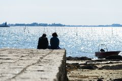Silhouettes of a couple sitting in front of the sea. PONTEVEDRA, SPAIN - APRIL 12, 2015: A couple on a stone pier in the village of Carril, in the Ria de Arousa Royalty Free Stock Photography