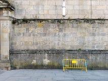 Pontevedra Spanien; 09/08/2018: Gammalmodig grå fasad Fasad för byggnadssten med det gula tillfälliga staketet arkivbilder
