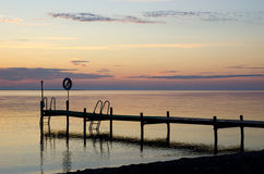 Ponticello del bagno con lifebouy in tramonto ed acqua calma Fotografia Stock