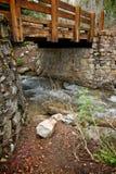 Ponticello di legno fra le pareti di pietra ed il flusso Fotografia Stock Libera da Diritti