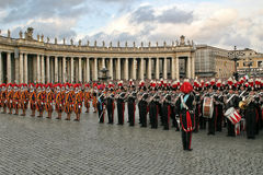 Pontifical Swiss guards and military band in Vatican. VATICAN - APRIL 19: Pontifical Swiss guards and military band stand on Saint Peter's Square during new stock photo