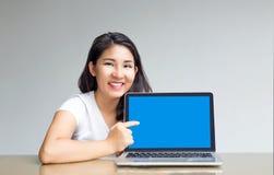 Ponto asiático da mulher para anular a tela do portátil para indicar foto de stock