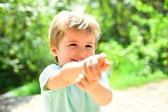Ponto bonito da criança em em algum lugar com a ajuda de seu dedo Criança feliz fora Emoções alegres de Scincere da criança fotos de stock royalty free