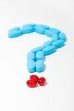 Ponto de interrogação azul e vermelho dos comprimidos Fotografia de Stock