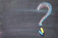 Ponto de interrogação colorido do giz no fundo do quadro-negro Fotografia de Stock