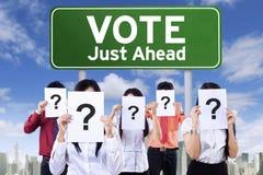 Ponto de interrogação da posse dos povos perto da placa de votação imagem de stock royalty free