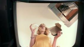 Ponto de vista do balde do lixo de uma jovem mulher que hesita quando entre o papel e o plástico ao reciclar vídeos de arquivo