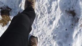 Ponto de vista do caminhante Close up de um movimento lento que anda no trajeto da montanha entre a grama e a neve
