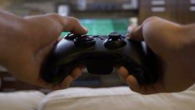 Ponto de vista do homem novo que desperdiça o tempo que joga o futebol no console do jogo de vídeo em casa - video estoque