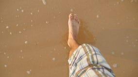 Ponto de vista do homem novo que pisa na areia dourada na praia do mar Pés masculinos que andam perto do oceano Pé desencapado do filme