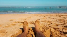 Ponto de vista dos pés do ` s do homem completamente da areia na frente da praia Imagens de Stock