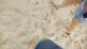 Ponto de vista dos pares novos que pisam junto na areia dourada na praia do mar Pés masculinos e fêmeas que andam perto do oceano video estoque