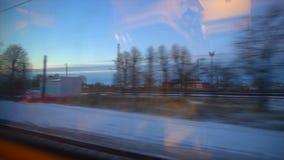 ponto de vista 4K da janela de um trem de passageiros A floresta abandonada do inverno move-se fora da janela vídeos de arquivo