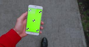 Ponto de vista, smartphone masculino da terra arrendada da mão com a tela vazia que anda na cidade video estoque