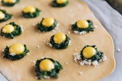 Ponto por ponto o cozinheiro chefe prepara o ravioli com queijo da ricota, ovos de codorniz das gemas e espinafres com especiaria foto de stock