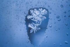 Ponto Thawed na janela congelada do inverno com teste padrão gelado dentro dele foto de stock royalty free