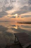 Ponton sur le lac au temps de coucher du soleil Photos stock