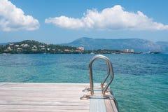 Pontoon on a beach of Ionian Sea, Corfu island. Wooden pontoon stretching into the sea in Greece, Corfu Royalty Free Stock Photo