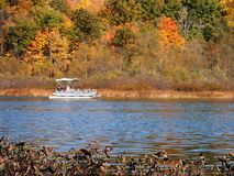 Pontoon Boat And Autumn Trees. Pontoon boat on a lake with orange and green autumn trees stock photos