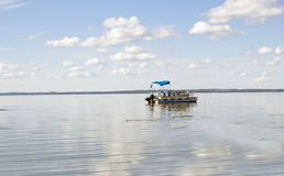 Pontoon boat coasting in a large body of water. Horizontal image of a pontoon boat coasting on a beautiful blue lake under clear blue sky in the summer time Royalty Free Stock Photography
