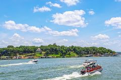 Pontoon boat full of people and two speedboats race down lake with luxury homes and docks on shore under bright blue sky with. Clouds and helicopter above stock photography
