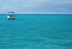 Pontoon Boat in the Ocean. A single pontoon boat in a calm tropical sea Royalty Free Stock Images