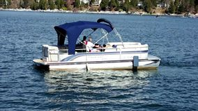 Pontoon boat pulling out of dock Lake Arrowhead Resort. Arrowhead Lake resort boating docks. Pontoon boat pulling out of dock turning into lake area stock video footage
