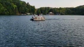 Pontoon boat sailing on a pond stock video footage