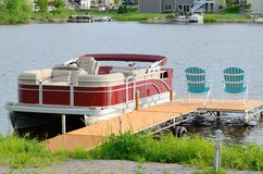 Pontoon Boat Tied to a Dock. Red Pontoon Boat Tied to a Dock With Two Chairs Stock Photography