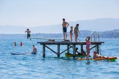 Pontoon bridge lake Geneva. Rolle, Switzerland - July 10, 2016: People having fun doing water sports on a beach near the city of Rolle, lake Geneva, Switzerland Stock Photos