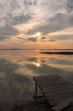 Pontoon on the lake at the sunset time. Wooden pontoon on the lake at the sunset time Stock Photos