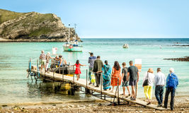 Pontoon at Lulworth Cove, Dorset, UK. The pontoon at Lulworth Cove in Dorset, on the South Coast of England. Tourists are boarding a small boat, which will take Royalty Free Stock Image